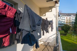 Hanging smoked damaged clothes on clothes line at the balcony