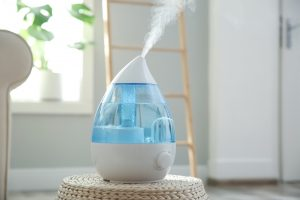 Modern air humidifier on wicker pouf indoors